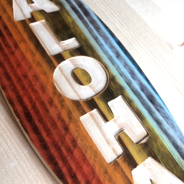 carved wooden surfboard with rainbow of colors