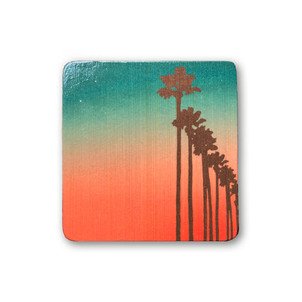 art block with palm tree silhouettes against ombre sunset sky