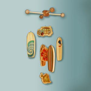 vintage woody car and surfboards hang from a crib mobile