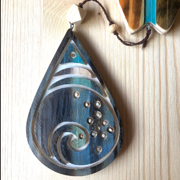 carved wooden wall hanging with surfboard, rainbow and ocean drop