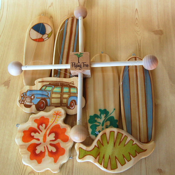 wooden surfboard and tropical themed baby crib mobile