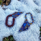 Two blue HAK knives in snow