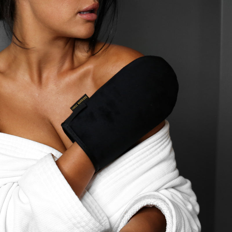 Woman applying tan to shoulder with Three Warriors Eco-Friendly Tanning Mitt.