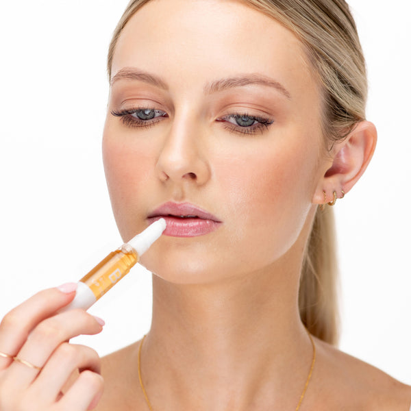Woman with blonde hair applying Biologi BL Nourish Lip Serum 5ml to her lips.