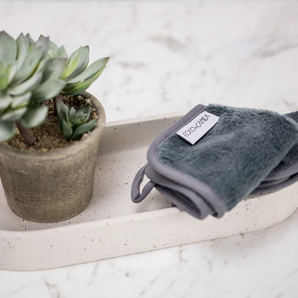Coco & Camila Original Cleansing Cloth folded up on a tray next to pottetd plant.