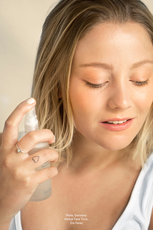Woman applying Ere Perez Herbal Face Tonic 100ml to her face.