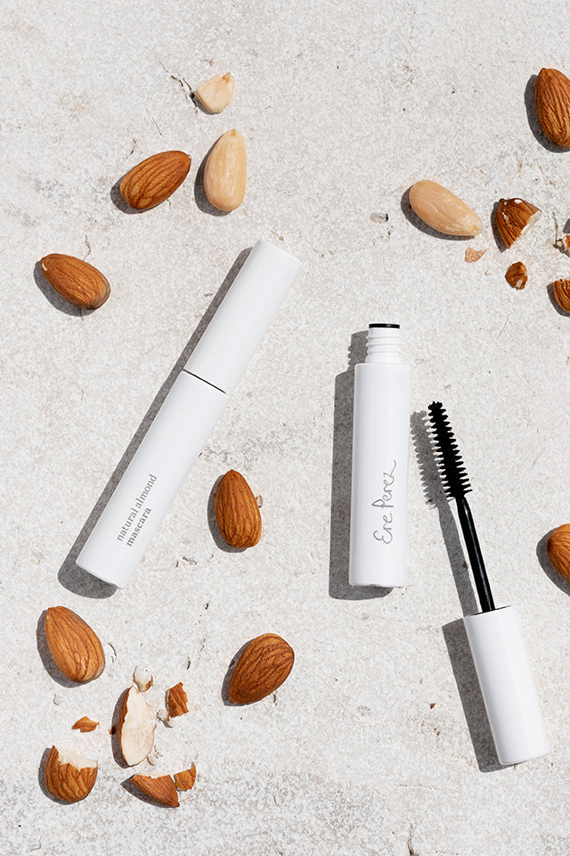 Ere Perez Natural Almond Mascara in Black surrounded by almonds.