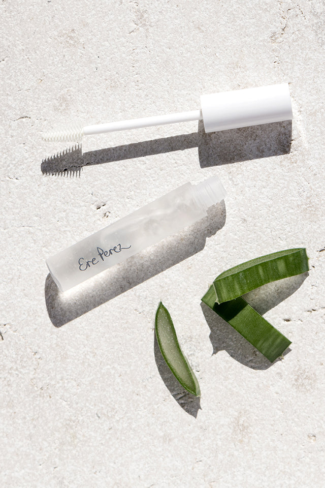 Ere Perez Lash and Brow Aloe Vera Gel Mascara in Clear opened and lying next to slices of Aloe Vera.