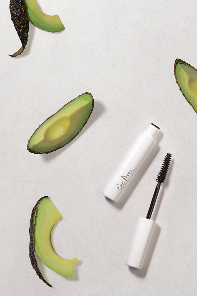Ere Perez Avocado Waterproof Mascara Black 10ml opened with brush, surrounded by Avocado slices.