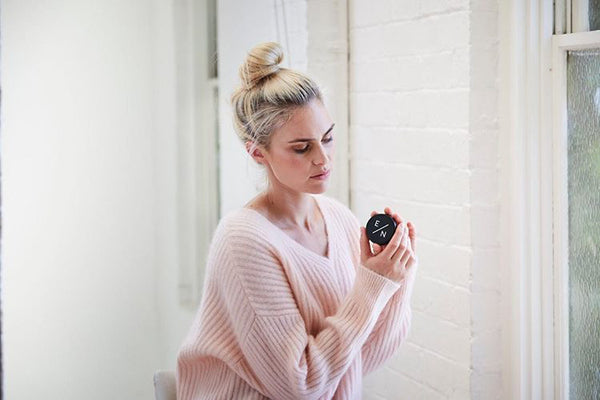 Woman in pink jumper holding Exposed Naturals Charcoal and Magnesium Deodorant tin.