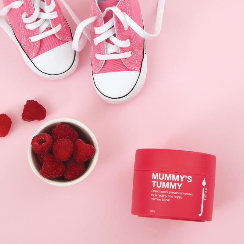 Skin Juice Mummy's Tummy Stretch Mark Prevention Cream 200ml pot next to a bowl of Raspberries and baby pink sneakers.
