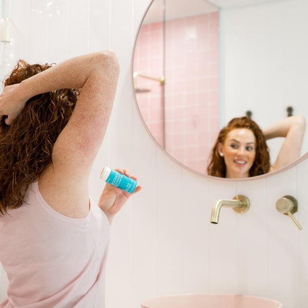 Woman applying Woohoo Body Deodorant and Anti-chafe Stick in Surf 60g to her armpit.