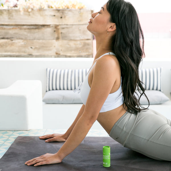 Woman stretching on a yoga mat next to Woohoo Body Deodorant and Anti-chafe Stick in Wild 60g.