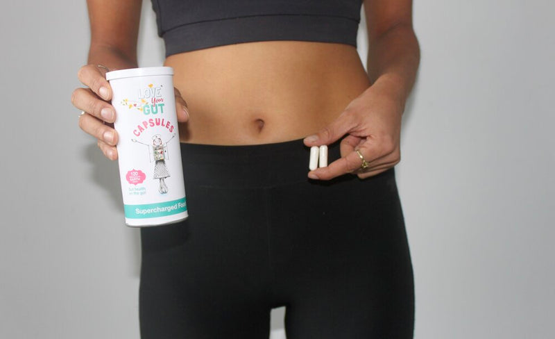 Woman holding Supercharged Food Love Your Gut Capsules tin and capsules in her hand.