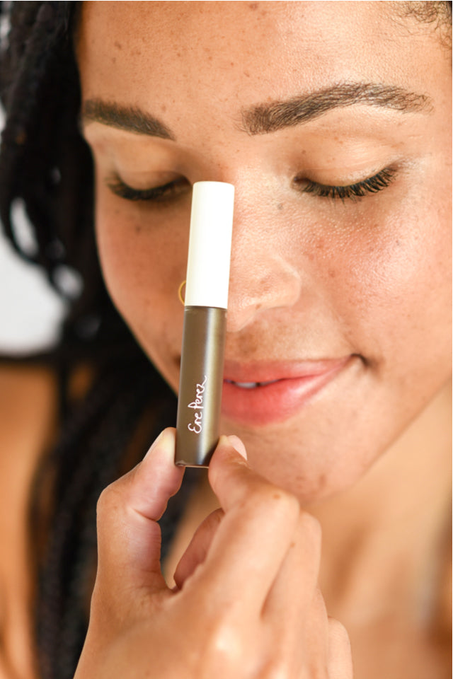 Woman holding the Ere Perez Argan Brow Hero in her hand after applying product to her eyebrows.