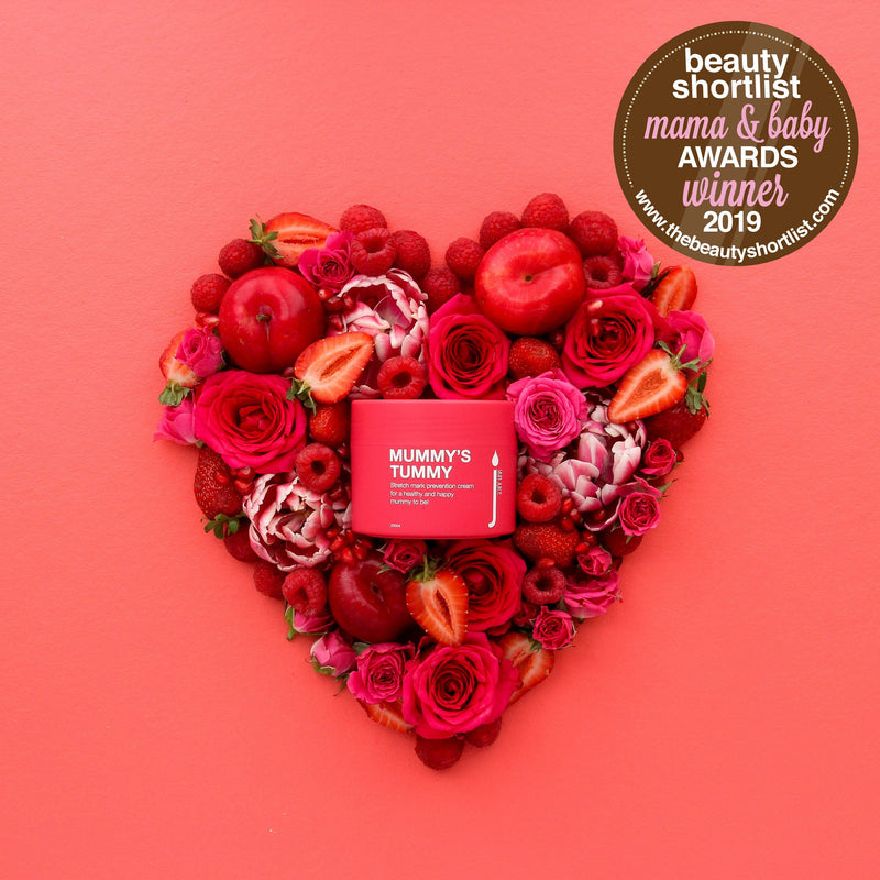 Skin Juice Mummy's Tummy Stretch Mark Prevention Cream 200ml pot surrounded by red roses and fruit in a heart shape. Beauty Shortlist Award Winner 2019.