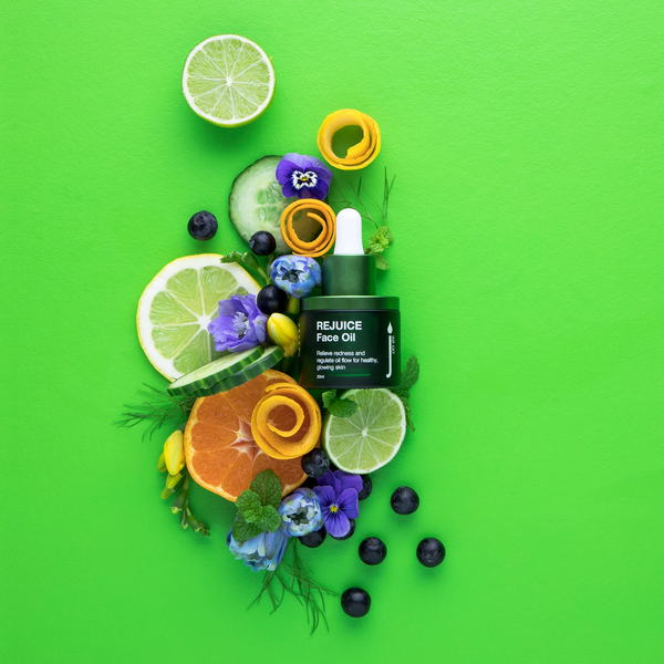 Skin Juice Re Juice Face Oil on green background surrounded by fruits and flowers.