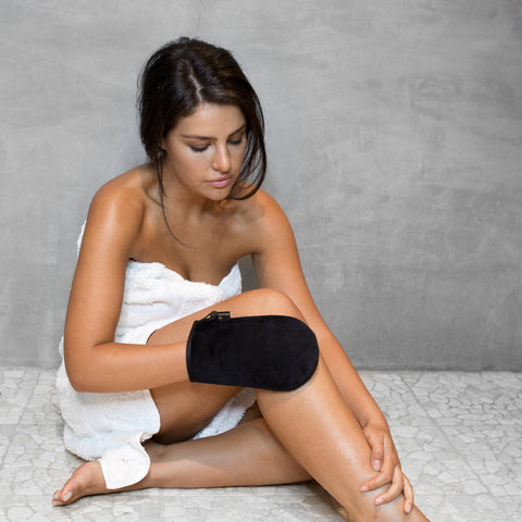 Woman in a white towel applying Three Warriors Tan to leg with Eco-friendly Tanning Mitt