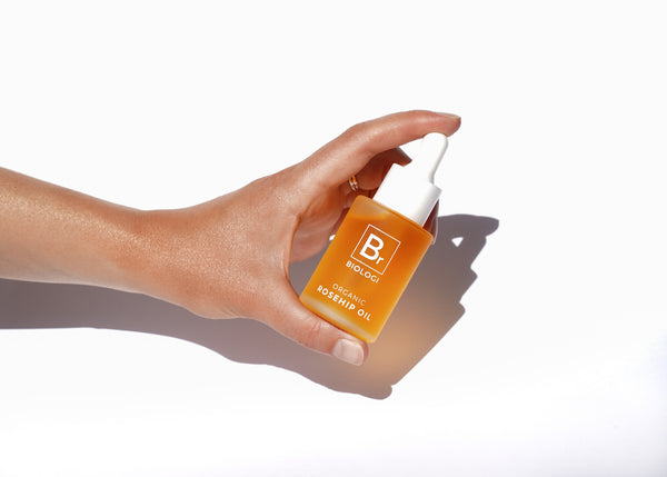Hand holding Biologi Serum Br Organic Rosehip Oil 30ml in glass bottle between finger and thumb.
