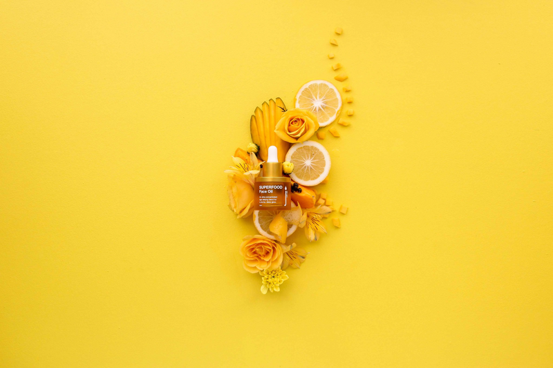Skin Juice Superfood Face Oil 30ml bottle surrounded by citrus slices and flowers on yellow background.
