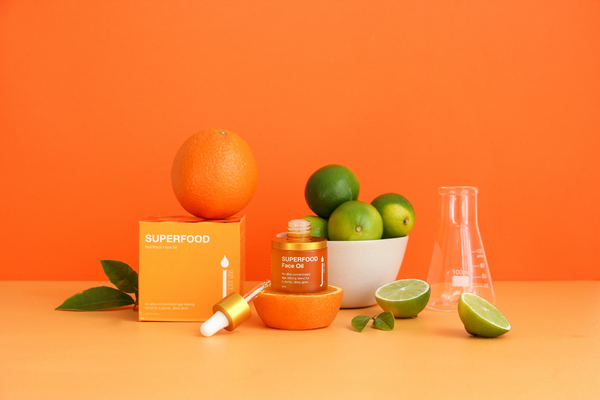 Skin Juice Superfood Face Oil 30ml bottle surrounded by box and citrus fruits with an orange background.