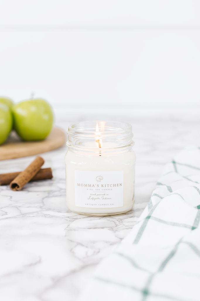 Momma's Kitchen Candle smells like... Momma's Kitchen is a warm and cozy blend of green apples, bright peach, and fresh pine, highlighted with a heart of cinnamon and notes of sweet balsamic spice.