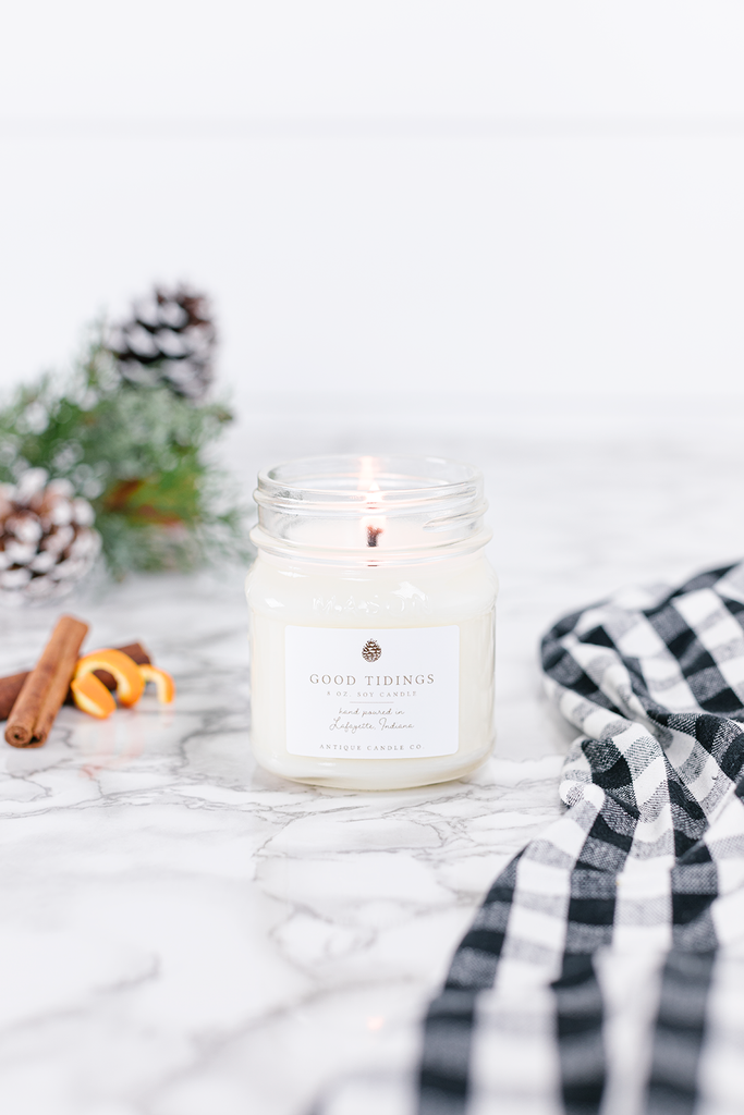 Good Tidings Candle smells like... Good Tidings is a warm holiday blend of evergreens, citrus, cinnamon, and clove, highlighted by a sweet musk of raspberry, maple, and vanilla.