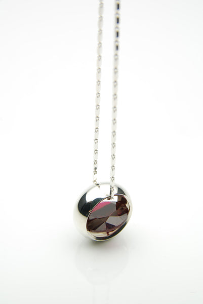 Laus pendant with a dark red garnet