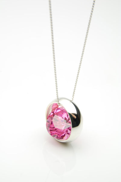 Laus silver pendant set with a large pink ruby that moves freely inside the silver band surrounding it