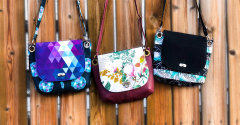 Multiple Jesse Crossbody bags hanging on a fence.
