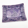 Purple peacock design on handmade pottery.