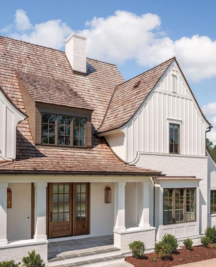 A French inspired modern white farmhouse with a light brown roof and windows