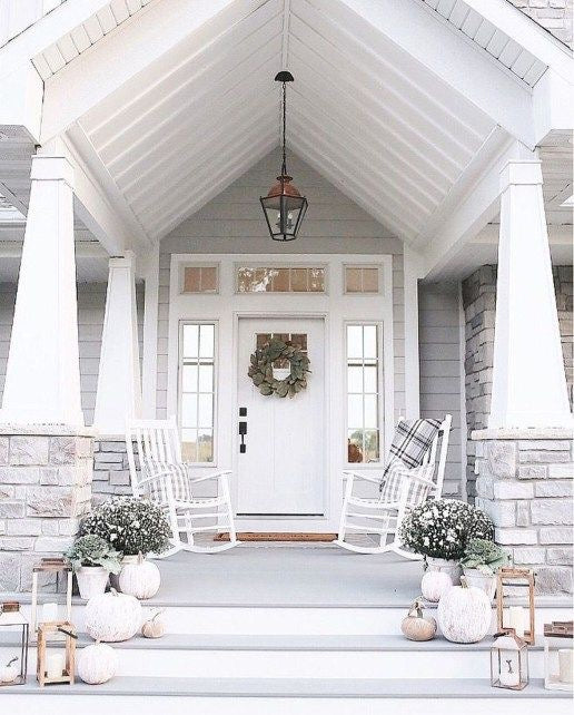 A light and lively front porch overhang with fall farmhouse decor and a magnolia wreath