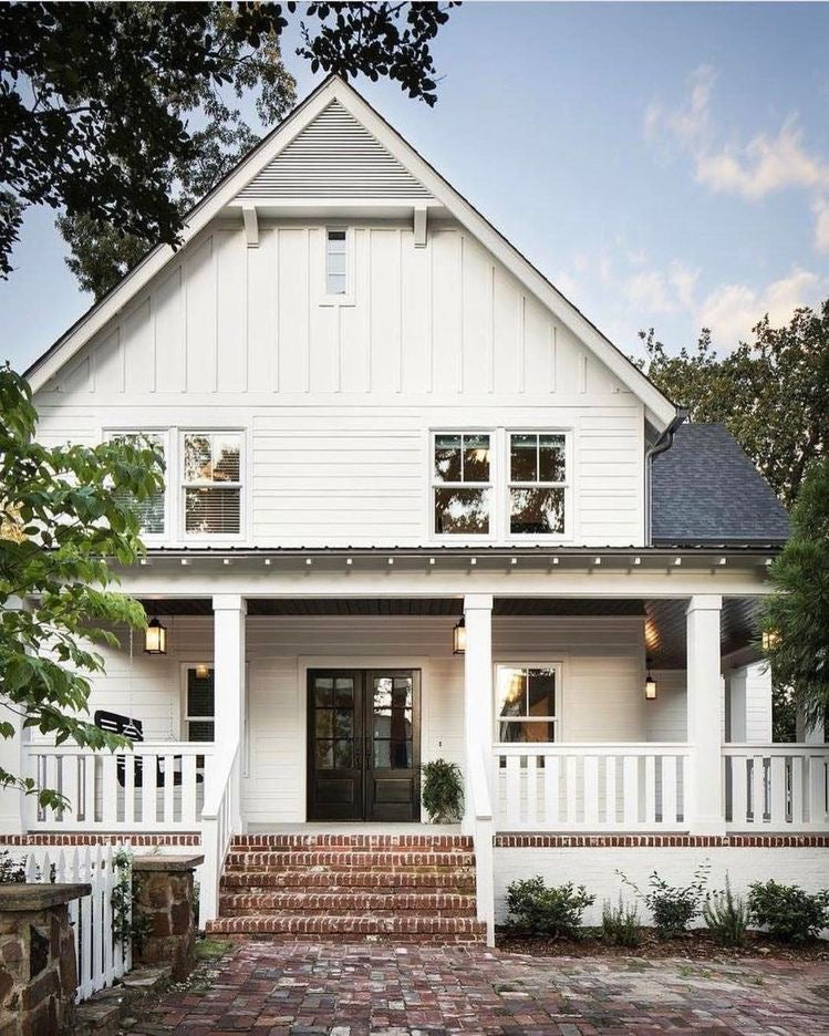 White modern farmhouse exterior with a brick patio and stairs