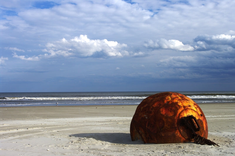 A big metal thing on the beach.  It is surely a mine.