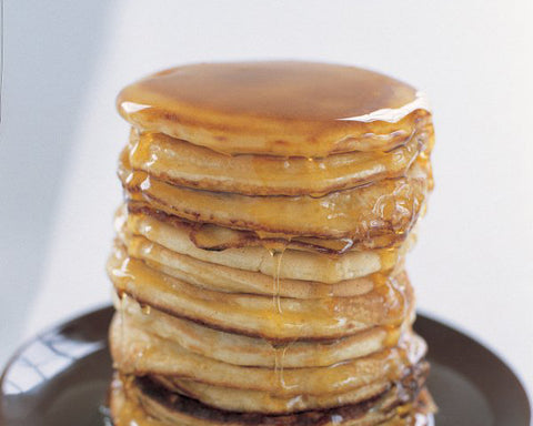 Fluffy american pancakes with maple syrup dribbling down the sides