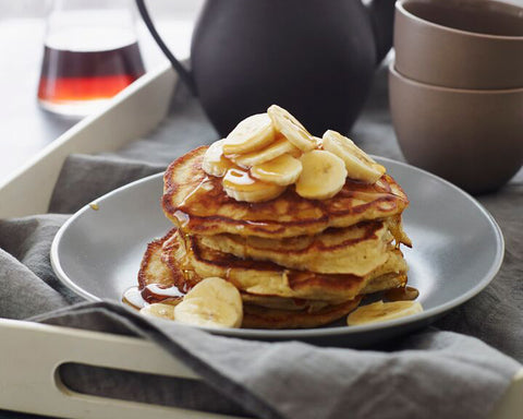 Fluffy Banana Pancakes with slices of banana piled on top then covered in syrup.