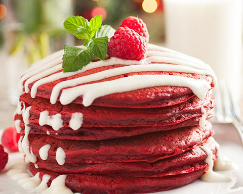 Red Velvet Pancake stack with white cream cheese glaze dribbling down the sides with a raspberry on top.
