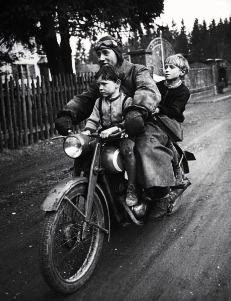 Photo by Walter Sanders. Munich, Germany, May 1949 of a man and his two boys riding on their daily commute.