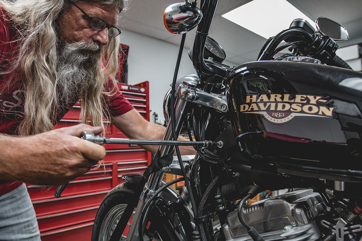 Todd using a extension for his socket to stay clear of the tank. He is using a 1/4 inch allen and a 1/2 wrench to take of the front tank bolt. Lowbrow-Customs-Cole-Foster-Gas-Tank-How-to-Install-4685