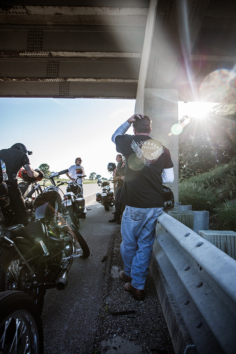 Jay filling his gas tank under an overpass. Lowbrow Customs - Cross Country 2016