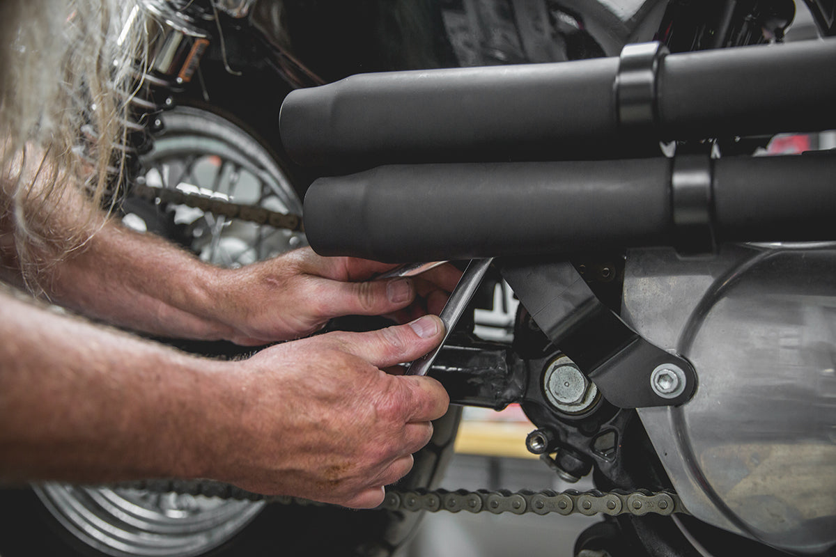 Todd using 2 - 1/2 in. wrenches to tighten the back tab bolts. Lowbrow-Customs-Cycle-Source-techtip-install-biltwell-mini-mufflers-6158