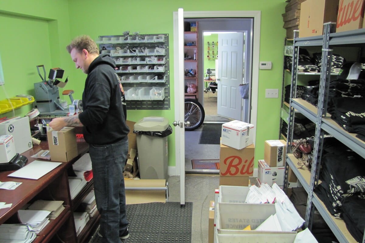 - Kyle packing some orders up to ship out. Through the door is the small bike workshop, and beyond that the office.