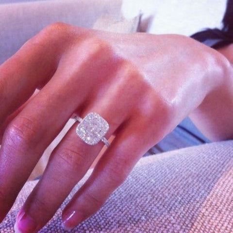 halo cushion cut diamond ring on hand
