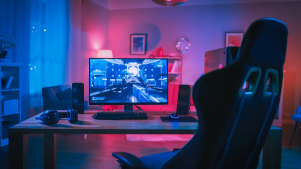 BEST GIFTS FOR TECHNOLOGY LOVERS: ACCESSORIES AND MORE, gaming desktop and chair in red and blue lighting