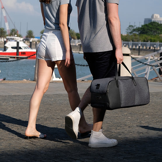 Flexpack Go by Korin - Functional Anti-Theft Duffle Bag easily hand carried, man and woman walking