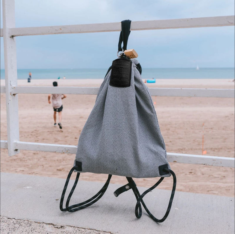 Loctote Flak Sack Sport I - Theft-Resistant Drawstring Backpack hung on a bar locked prevent theft
