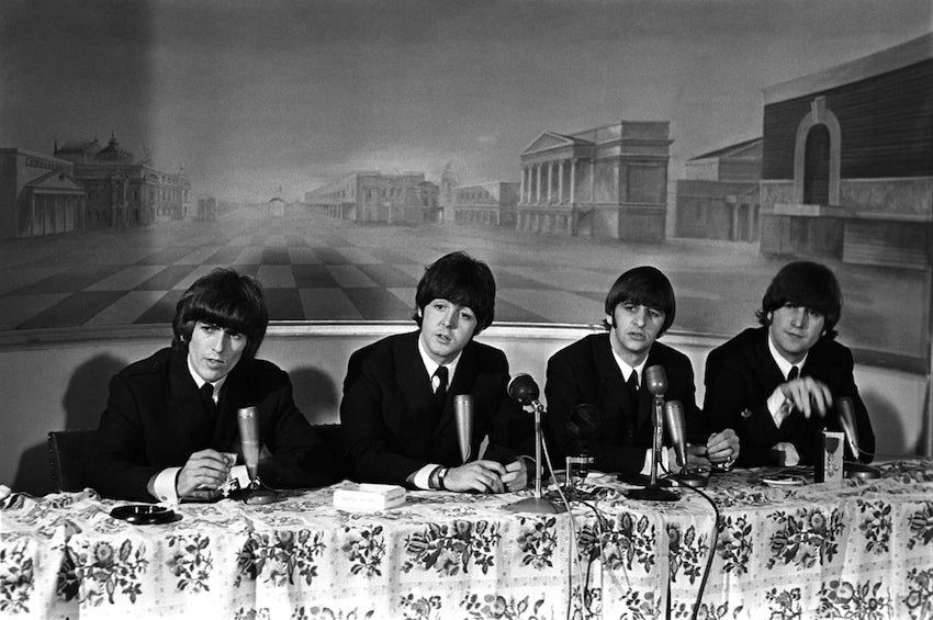 The Beatles at a press conference while on tour in the 60s