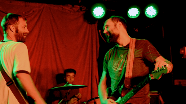 Doug Martsch chats with his bass player on stage with Built to Spill.