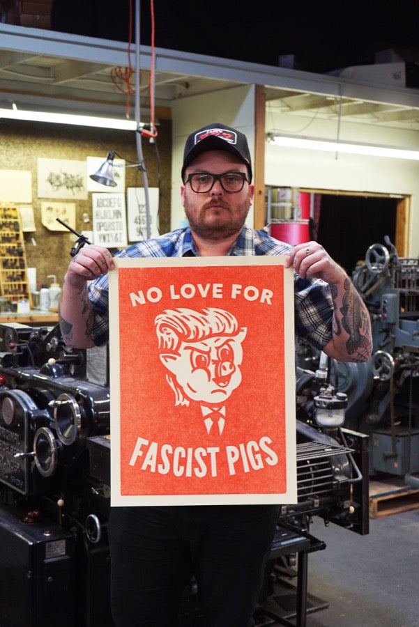 "Printmaker Carl Carbonell holding his art ""No Love For Fascist Pigs"""